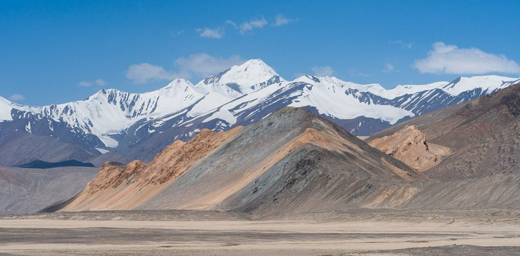 Colorfull mountains and snowcapped mountains around the dessert landscape of the Pamir Plateau