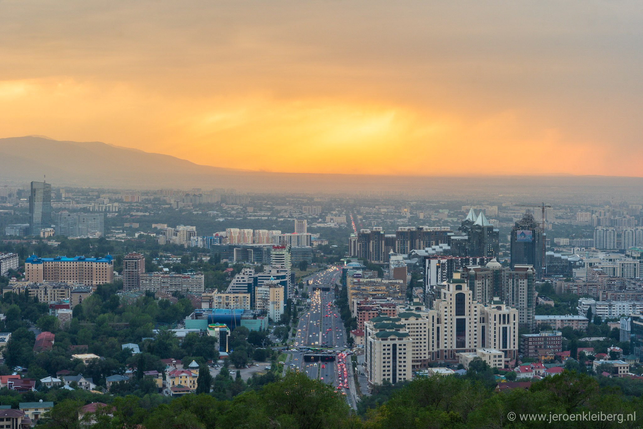 An orange sun lights the evening sky above Almaty